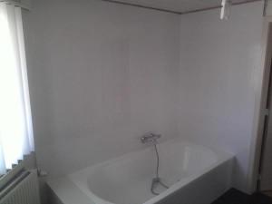 Witte wandtegels aan bad