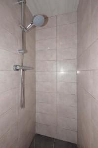 langwerpig beige tegel in douche